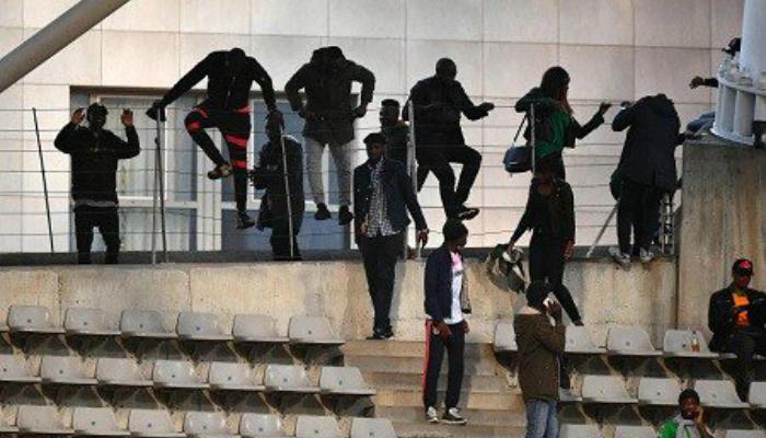 Fans climbing fence into stadium