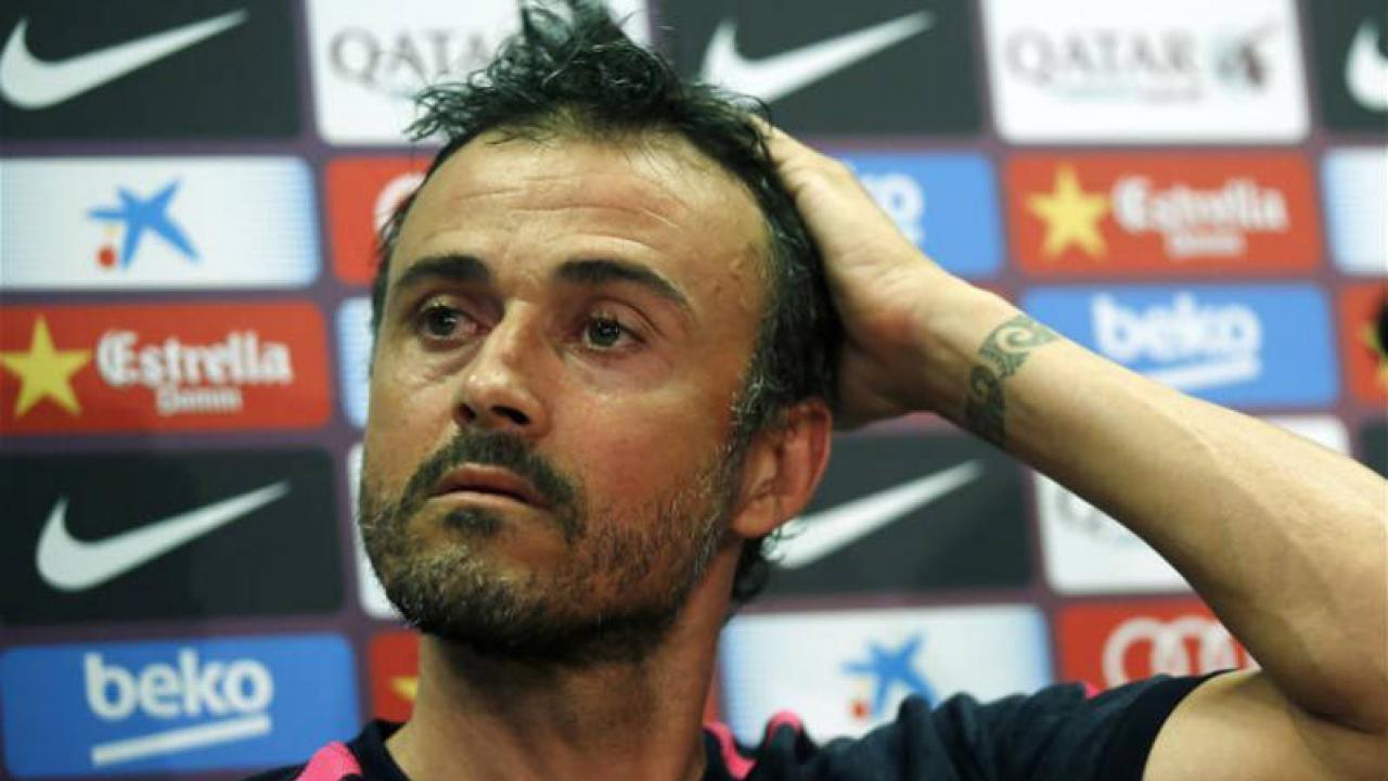 Luis Enrique rubs his head at a press conference