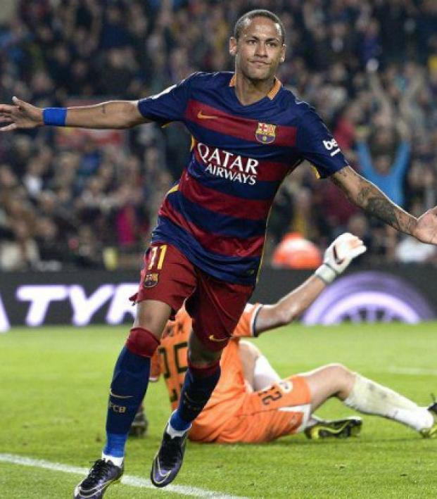 Neymar celebrating scoring a goal with his arms oustretched.