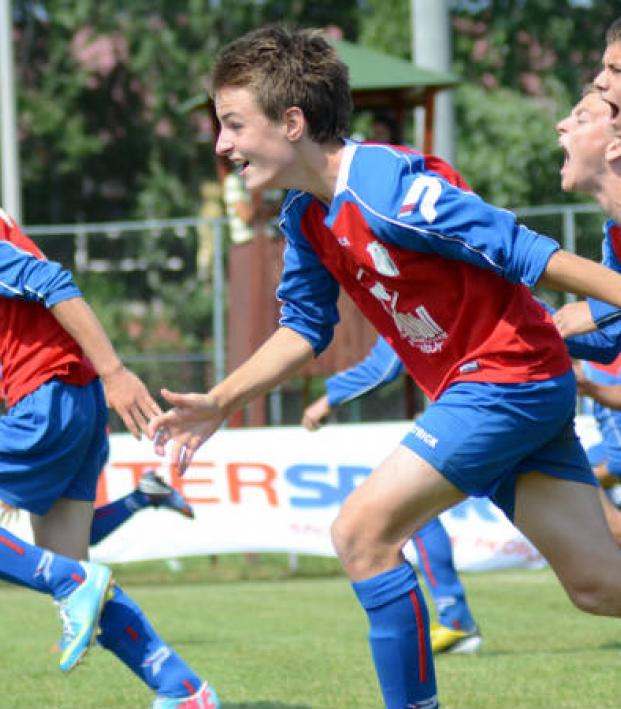 Teenage youth soccer players run down the field