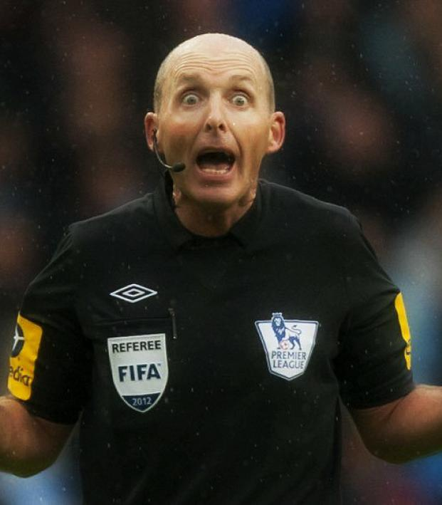 Referee yelling back at the screaming fans.