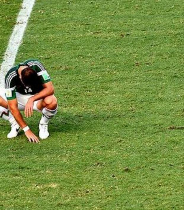 A Mexican player crouches on the field, defeated, after a last minute loss to Holland