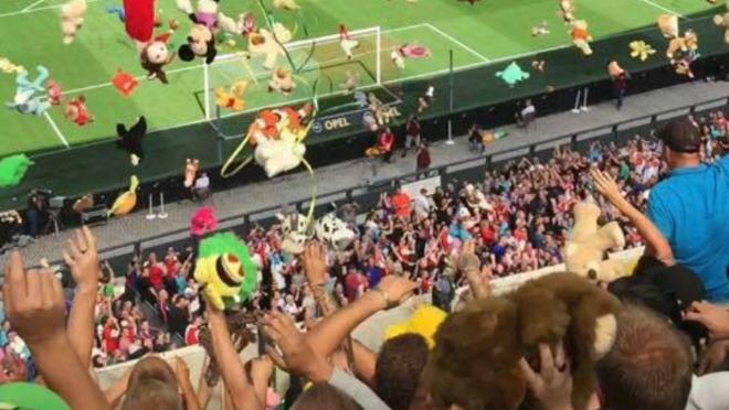 ADO Den Haag fans throw stuffed animals.