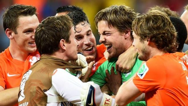Dutch players swarm backup keeper Tim Krul after his game-winning save