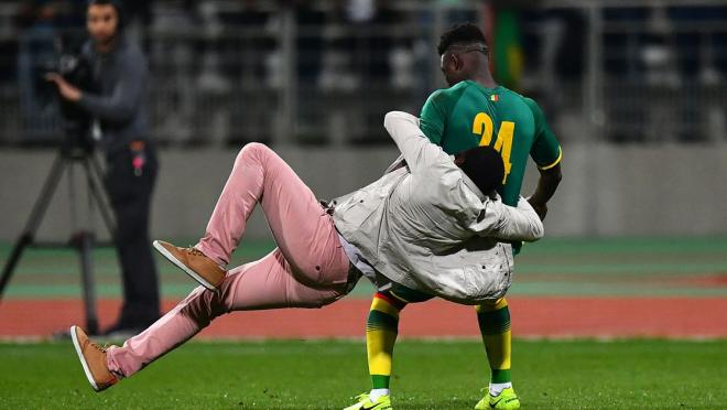 Senegal's Lamine Gassama is tackled by a fan.