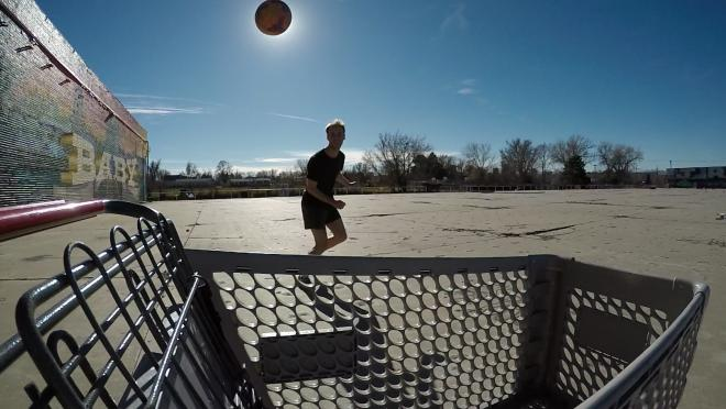 A small tattooed boy heads a soccer ball past the sun as it eclipses into a shopping cart