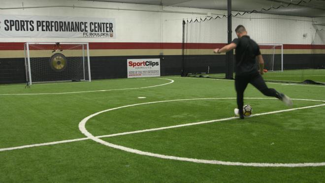 Leigh kicks at ball at a gong.