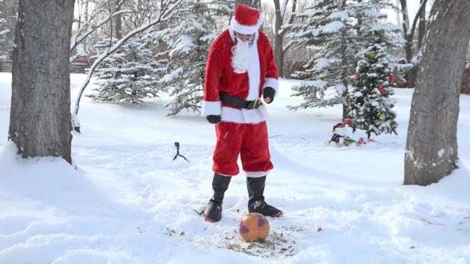 Santa fails at an attempt to kick over a Christmas tree.