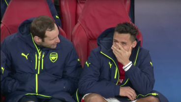Alexis Sanchez laughs as Bayern Munich scores their 5th goal against Arsenal